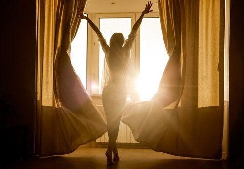 Kvinde foran sollys fra vindue