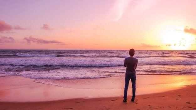 Mand med usikker-ambivalent tilknytning står og ser ud over hav