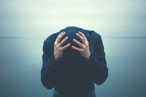 Mand, der har problemer med at bekæmpe angst, tager sig til hoved