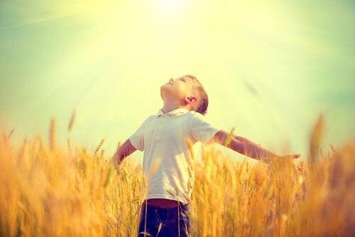 Dreng på mark kigger op mod solen