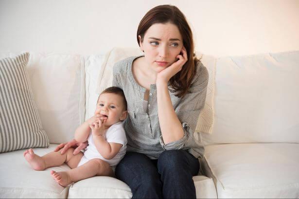 Mor sidder i sofa med baby med undvigende tilknytning