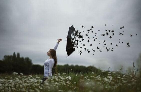 Kvinde med paraply, der bliver til blade