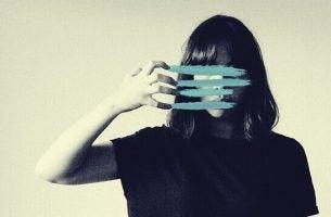 Kvinde med blå streger som kradsemærker foran ansigt