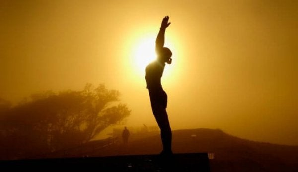 Kvinde dyrker tai chi foran sol