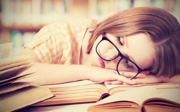Kvinde ligger ovenpå bøger, da hun ikke kan modstå behov for at sove