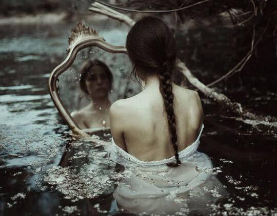 Kvinde i flod ser sig selv i spejl