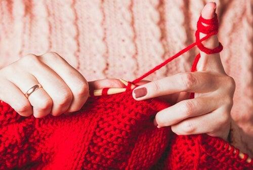 Kvinder nyder strikning med rødt garn