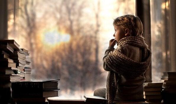 Dreng kigger ud af vindue