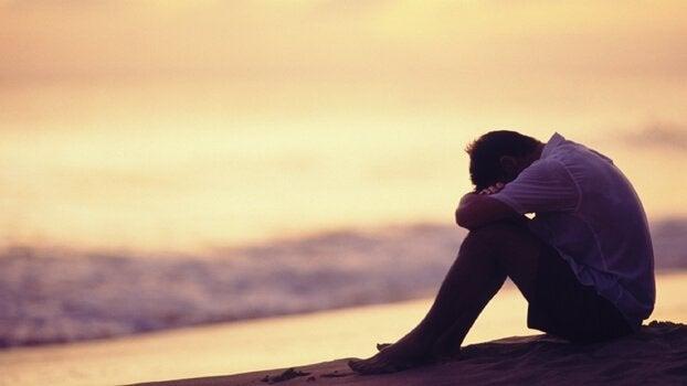 Mand uden en familie sidder ensomt ved hav