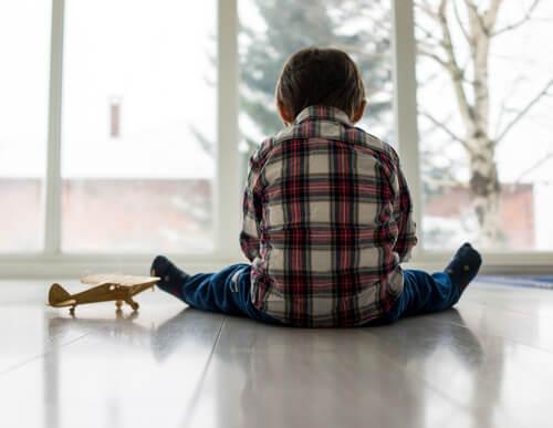 Dreng med autsime sidder alene på gulv