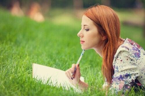 Kvinde ligger i græs og fører dagbog over påtrængende tanker