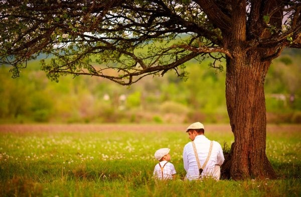 Far og søn sidder under træ