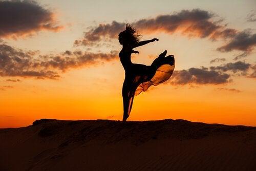 Kvinde hopper foran solnedgang som tegn på frihed