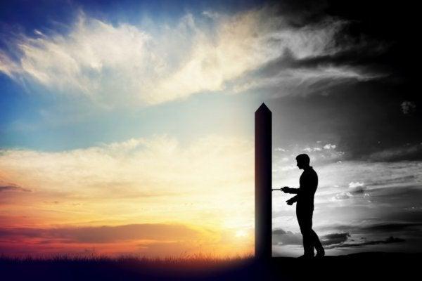 Mand står ved mur foran landskab