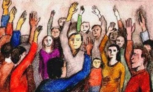 Folk med hænderne oppe viser, hvordan grupperfølelser kan gøre os voldelige