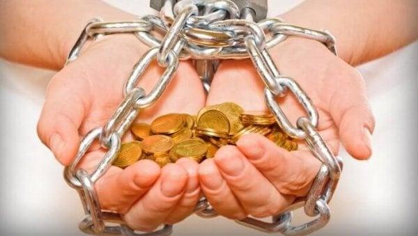 Hænder fyldt med mønter bundet i kæder