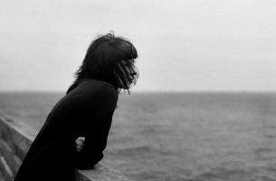 Kvinde kigger ud over hav og tænker over det svære ved at sige farvel