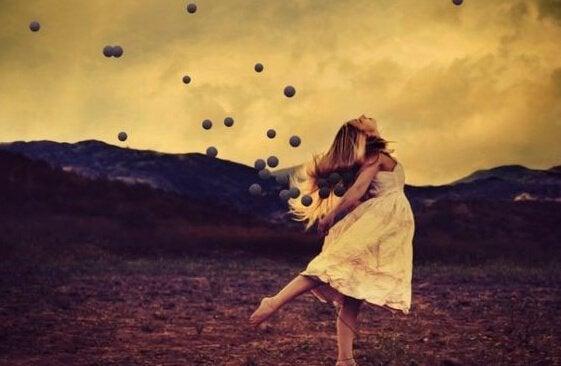 Kvinde på mark med bolde flyvende omkring sig