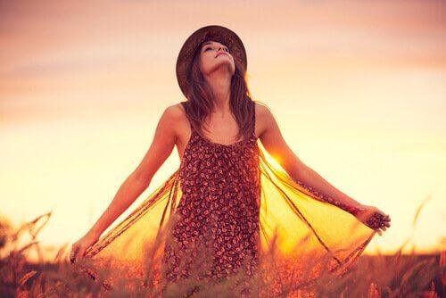 Kvinde på eng i sollys tror på, at hun kan gøre hvad som helst