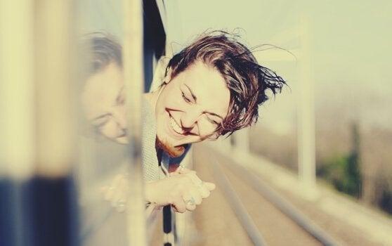 Smilende kvinde i tog nyder at rejse alene
