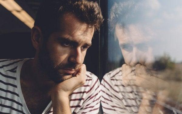 Deprimeret mand med paranoid personlighedsforstyrrelse ser ud af vindue