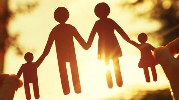 Papirsklip af familie foran sol