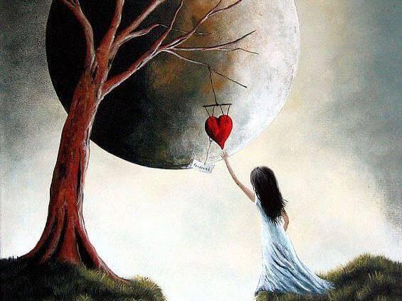 Lille pige rækker ud mod hjerte, der hænger i træ