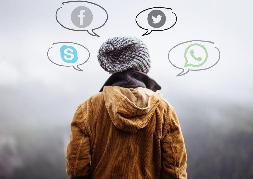 Person med talebobler omkring sig med ikoner fra sociale medier på grund af afhængighed af teknologi
