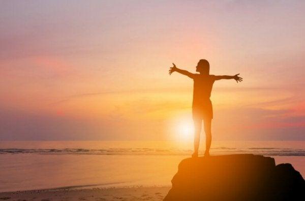 Kvinde på klippe foran solopgang nyder følelsen af serotonin og dopamin