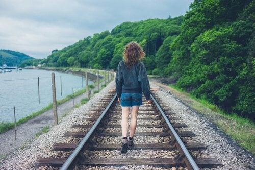 Kvinde går på togskinner og satser på, at hun ikke går glip af noget i livet