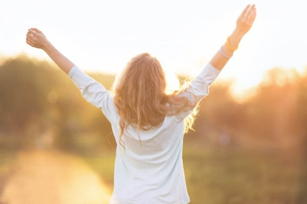 Kvinde med armene i vejret vælger at værdsætte livet i solen
