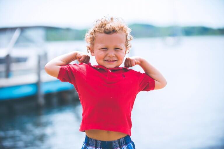 Barn viser, hvor stærk han er, med sine arme