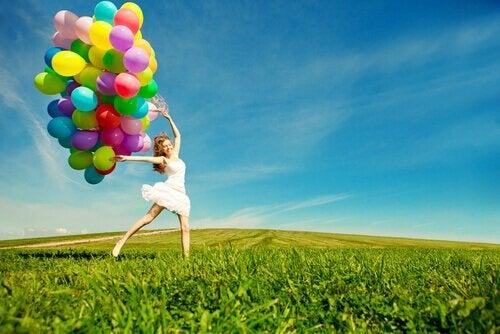 Kvinde, der hopper på mark med balloner, er eksempel på legende person