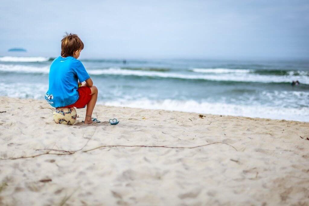 Barn sidder alene på strand og kigger ud på horisonten