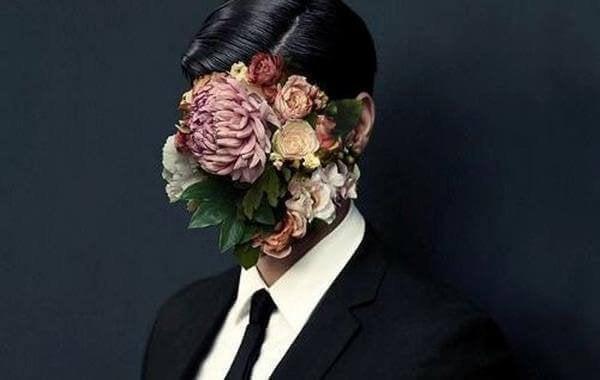 Mand med blomster foran ansigt