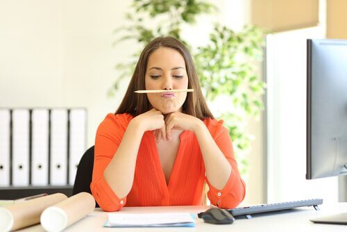 Kvinde på kontor med blyant under næsen er eksempel på legende person