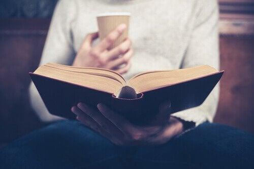 Person med kaffekop læser selvhjælpsbøger