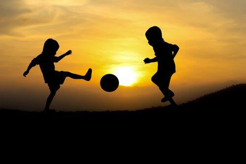 Børn spiller bold foran sol