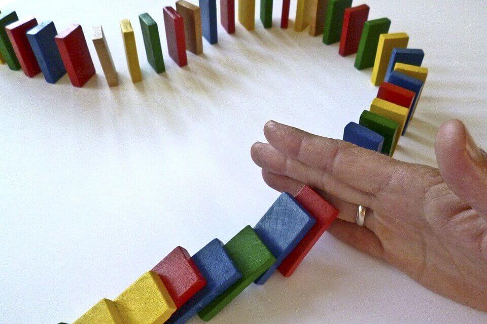 Person sætter hånd ned mellem dominobrikker