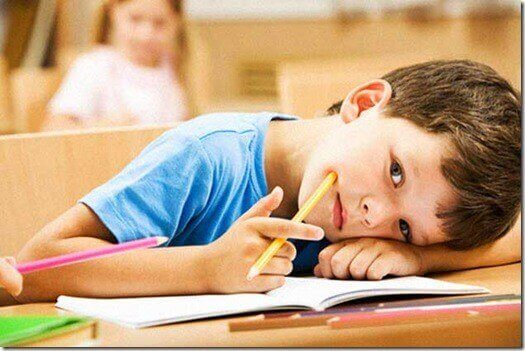 Dreng hviler hoved på bord i skole