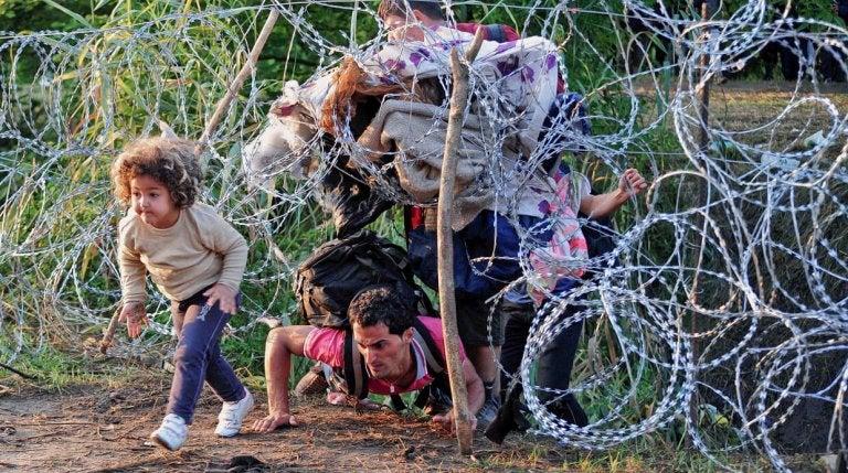 Far og barn er flygtninge og kravler gennem hegn