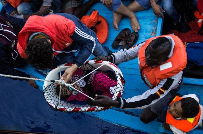 flygtningebarn hjælpes over på båd