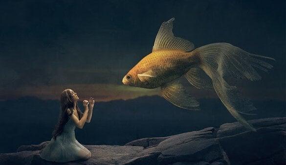 Pige ligger på knæ foran guldfisk