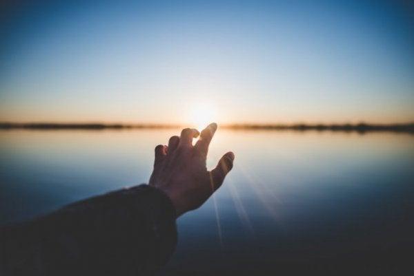 En hånd rækker ud over vand for at genvinde positiv energi