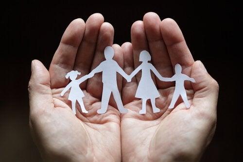Hænder bærer familie af papirsklip som symbol for systemisk terapi
