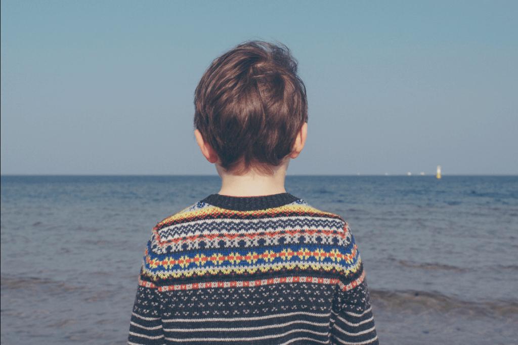 Dreng står og ser ud over hav