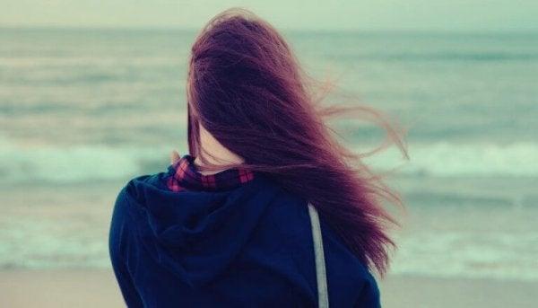 Kvinde står og kigger på havet