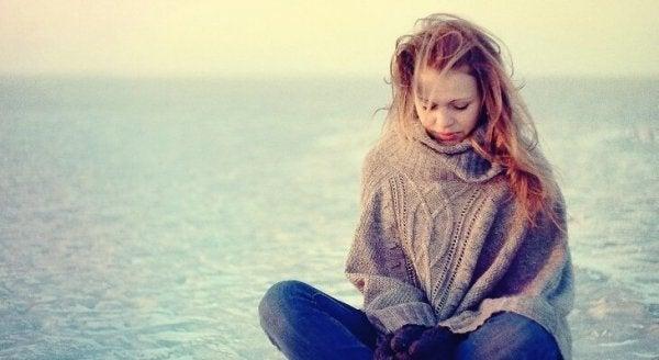 Kvinde sidder ved havet