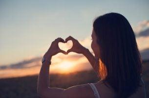 """Kvinde danner hjerte med hænder for at sige """"du skal passe på dig selv"""""""
