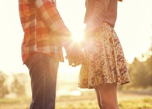 Par holder i hånd foran sol